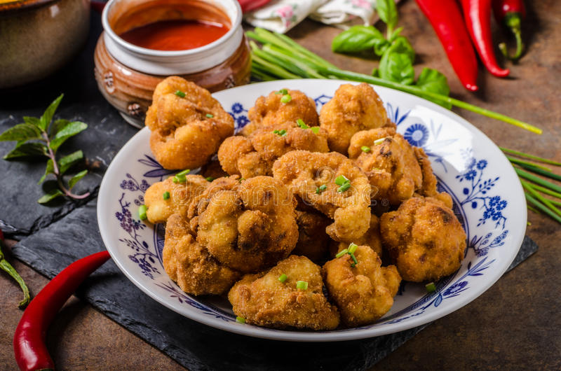 Breaded fried cauliflower. With roasted potatoes with herbs royalty free stock photo