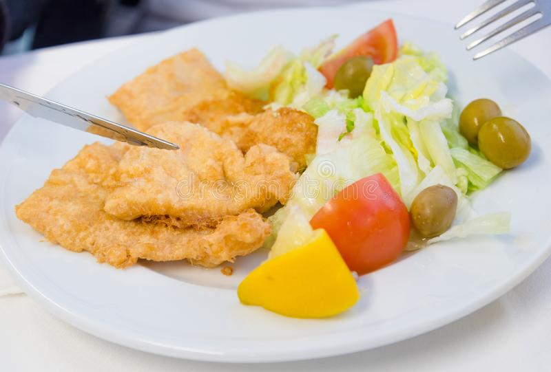 Breaded fried fish with fresh salad stock image