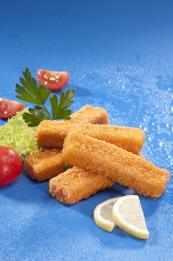 Breaded fritou dedos de peixes com o tomate do vermelho da alface e de cereja com fatia do limão no fundo azul com respingo da ág fotografia de stock