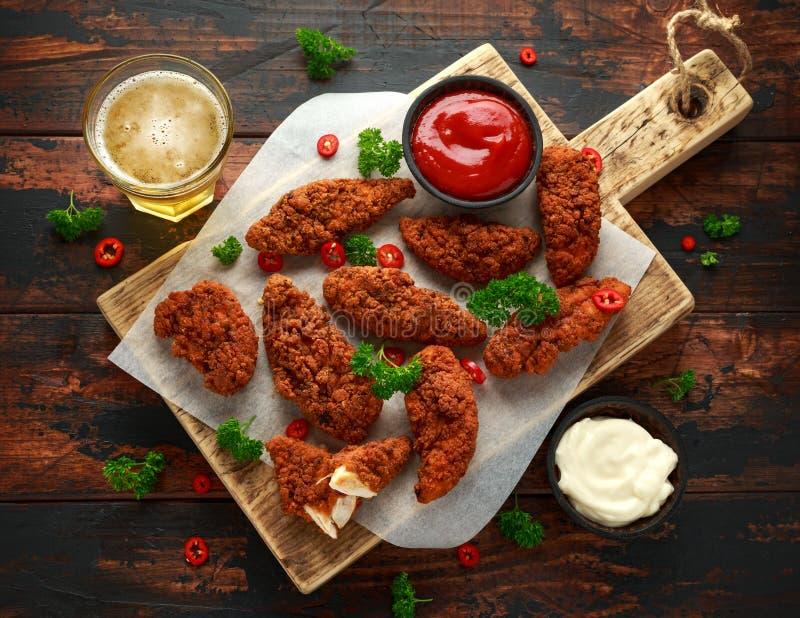 Breaded kurczak obdziera z piwem, ketchupem i majonezem na drewnianej desce, zdjęcia stock