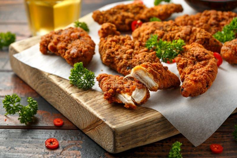 Breaded kurczak obdziera z piwem, ketchupem i majonezem na drewnianej desce, obraz royalty free