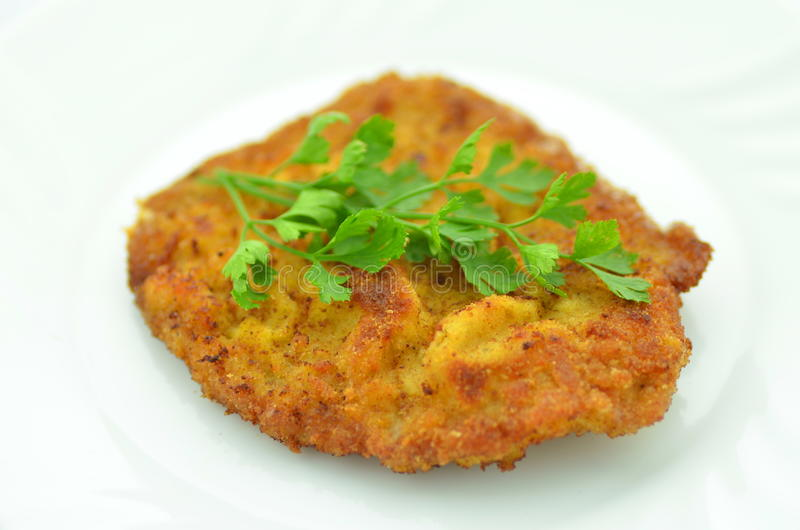 Breaded pork chop on a plate royalty free stock image