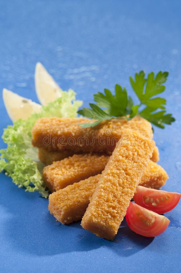 Breaded smażył Rybich palce z sałatą i czereśniowej czerwieni pomidorem z cytryna plasterkiem na błękitnym tle z wodnym pluśnięci zdjęcie royalty free