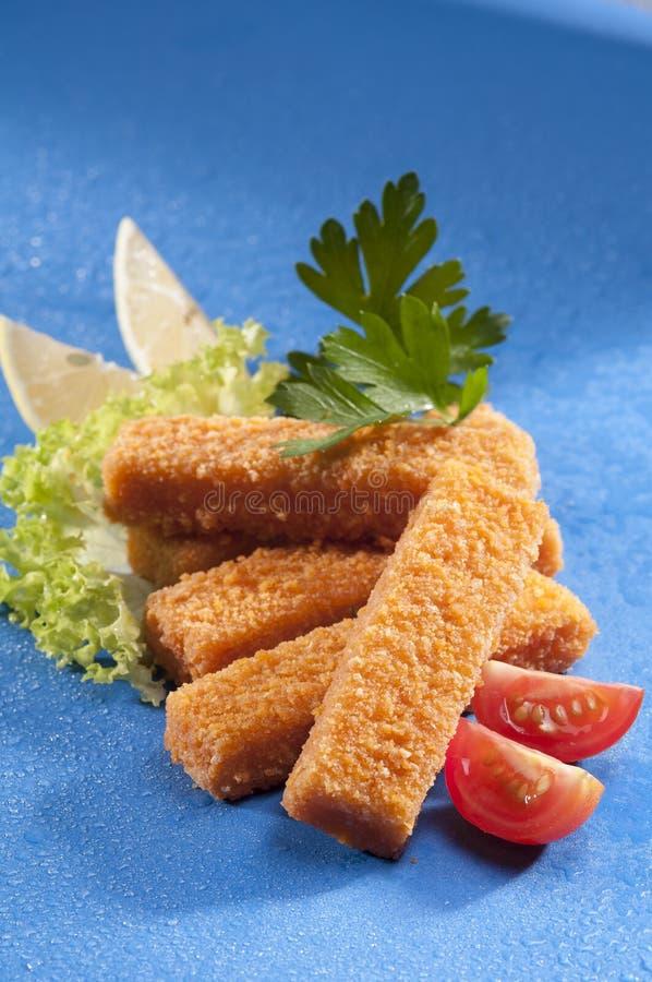 Breaded smażył Rybich palce z sałatą i czereśniowej czerwieni pomidorem z cytryna plasterkiem na błękitnym tle z wodnym pluśnięci obrazy royalty free