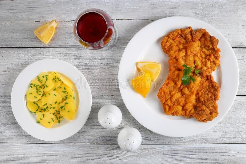 Breaded veal cutlets with potato salad. Delicious golden brown classic Wiener schnitzel - or breaded veal cutlets served on white plate with lemon slices on stock image