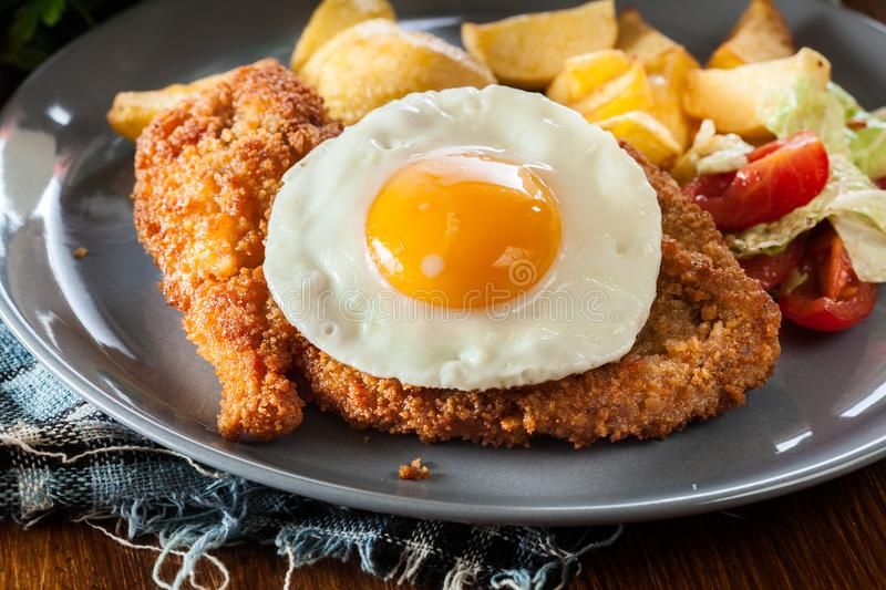 Breaded viennese schnitzel with fried agg stock images