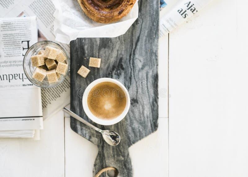 Breadroll dinamarquês do café com café e jornal fotos de stock