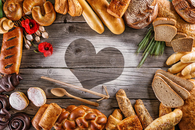 Breads, pastries, christmas cake on wooden background with heart, picture for bakery or shop, valentines day royalty free stock photography