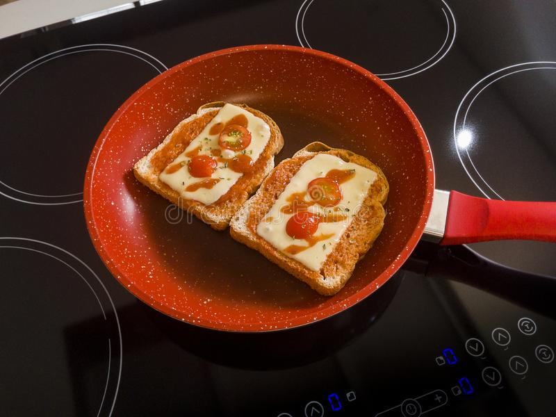 Breads in the Red Frying Pan on the Induction Cooktop.  stock images