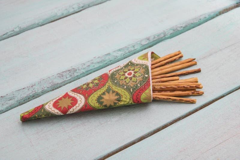 Breadsticks en una taza en un fondo de madera fotografía de archivo