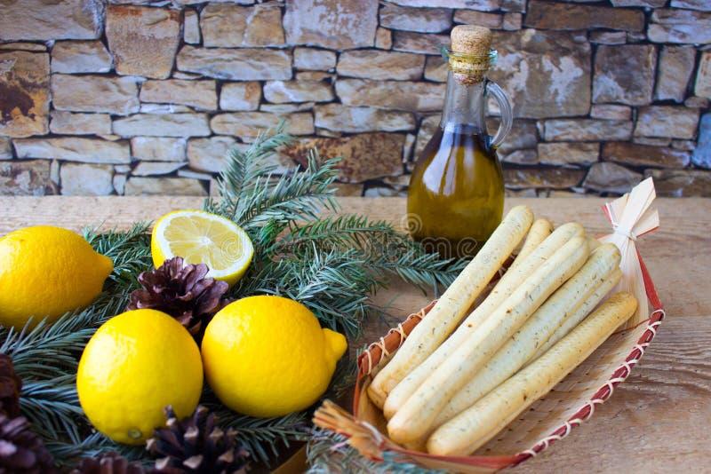 Breadsticksgrissini op rieten plaat, citroenen, en olijfolie royalty-vrije stock foto's