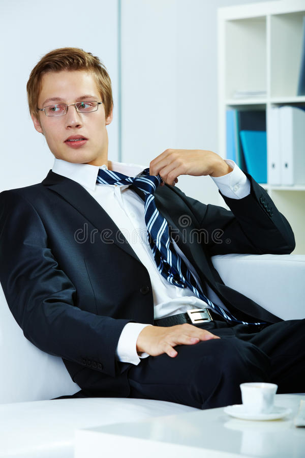 During break. Portrait of a successful employer at workplace untying necktie royalty free stock images