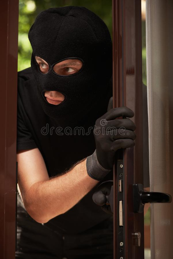 Break-in of an apartment. Thief in mask royalty free stock images