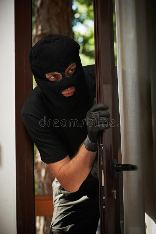 Break-in of an apartment. Thief in mask stock photo