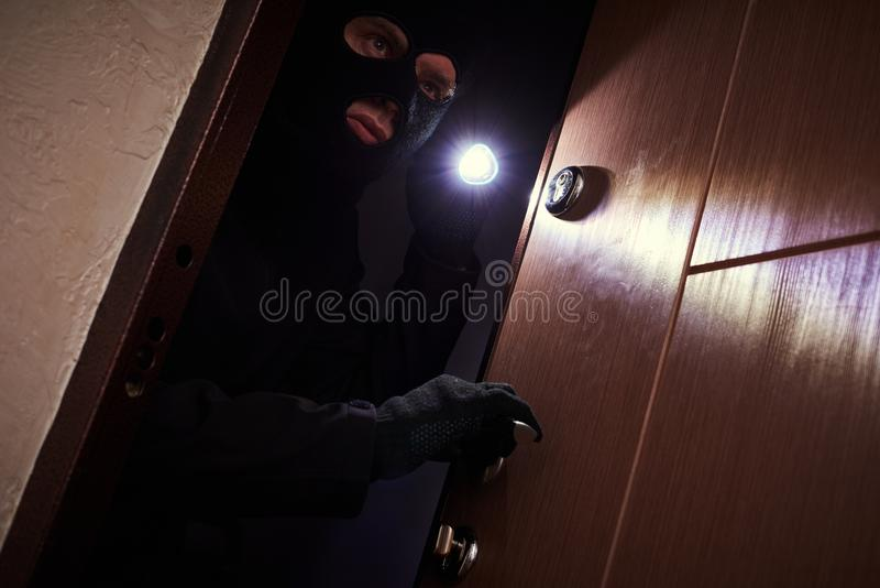 Break-in of an apartment. Thief in mask with flashlight stock images