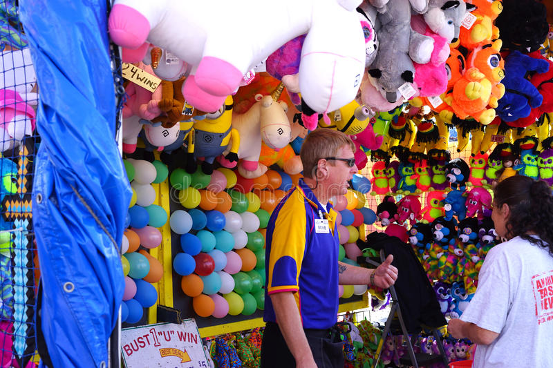 Break a balloon carnival game. There are many different games and prizes to be won along a carnival midway area. Carnies are the workers at carnivals stock photos