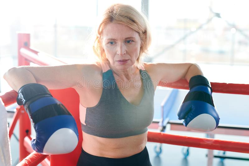 Break on boxing ring. Tired blonde sportswoman in boxing gloves leaning by border of boxing-ring while taking break between workouts stock images