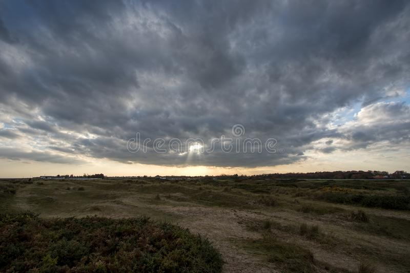 A break in the clouds. Bleak landscape with distant sun breaking. A break in the clouds. Hope for future weather as rays of sunshine appear on the horizon. Bleak stock image