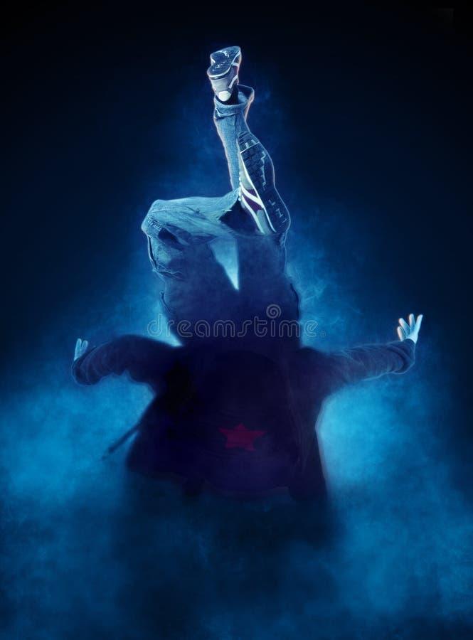 Break dance del hombre joven en fondo oscuro del humo imagen de archivo libre de regalías