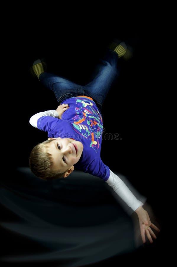 Break dance feliz de 6 años del muchacho/giro en fondo negro fotos de archivo