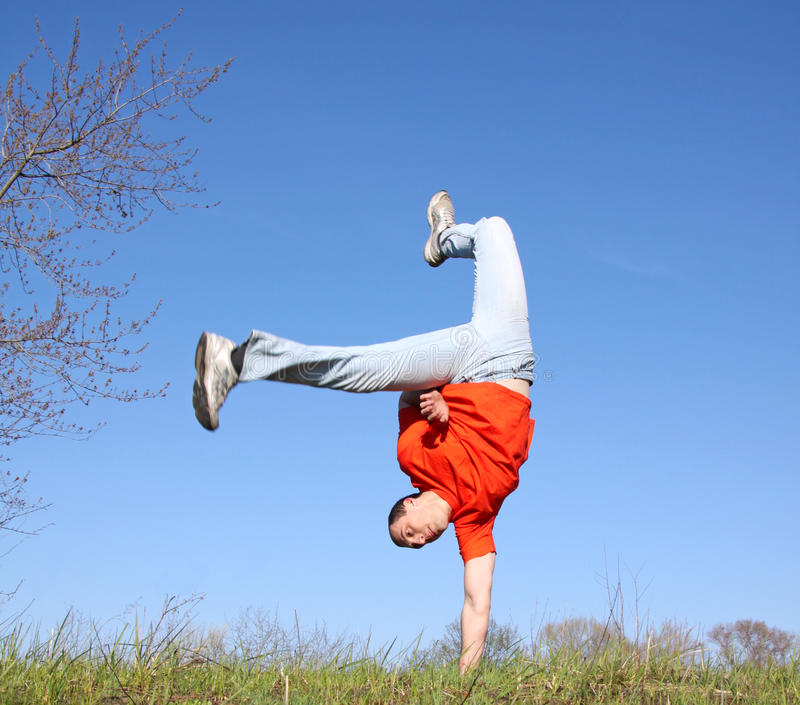 Break dance on the grass. Man in red t-shirt stock photos