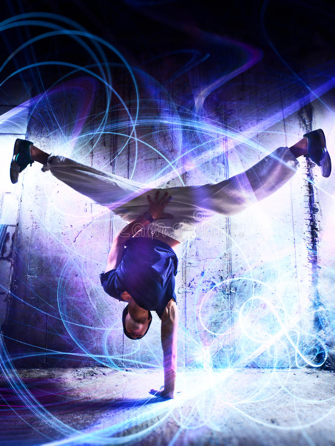 Break dance. Young man break dance on wall background. With light effects stock photos