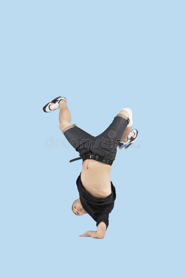 Break dancer on one arm over blue background royalty free stock image