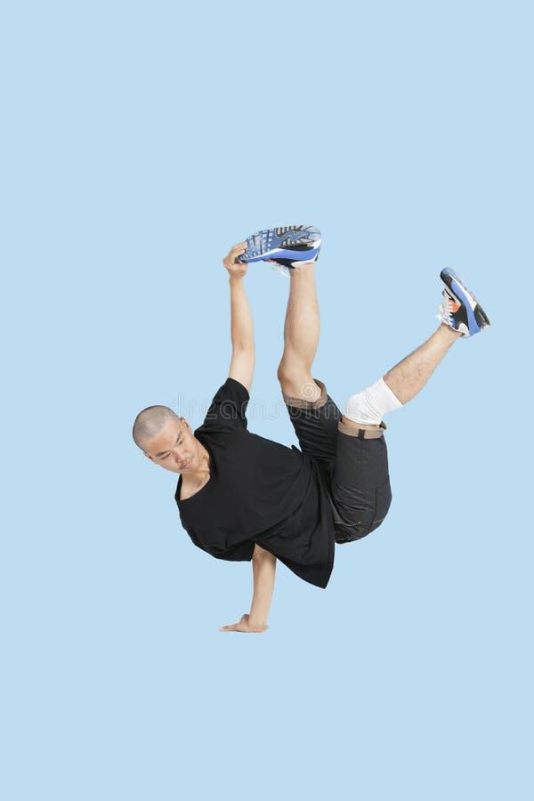 Break dancer performing handstand over blue background stock photos