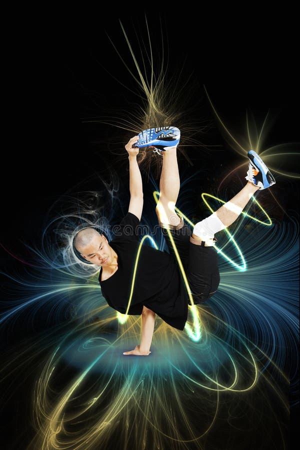 Break dancer performing handstand over blue background stock images
