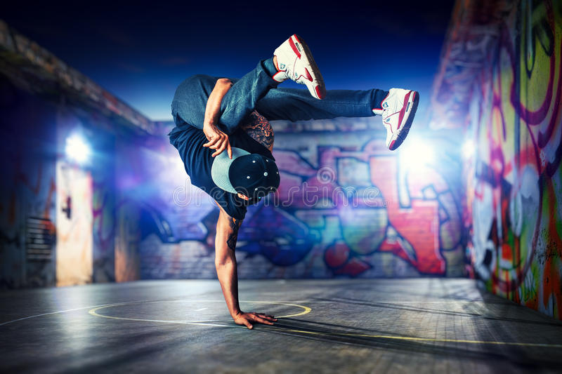 Break dancing outdoors. Young man break dancing at night on urban painted walls background royalty free stock photo