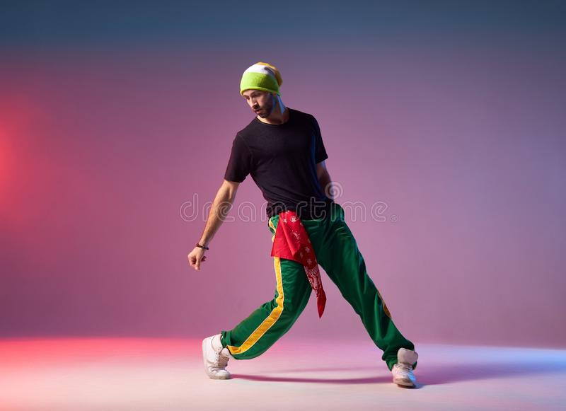 Break danser practicing in studio. Professional breakdancer in motion on studio stage, performing energetic dance, looking down, exercising with strength to win stock photos