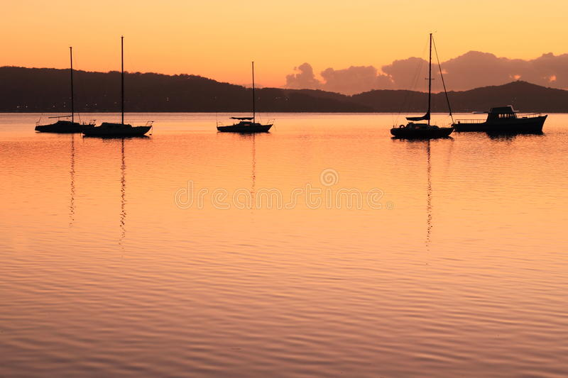 Boat silhouettes by golden sunrise royalty free stock photos
