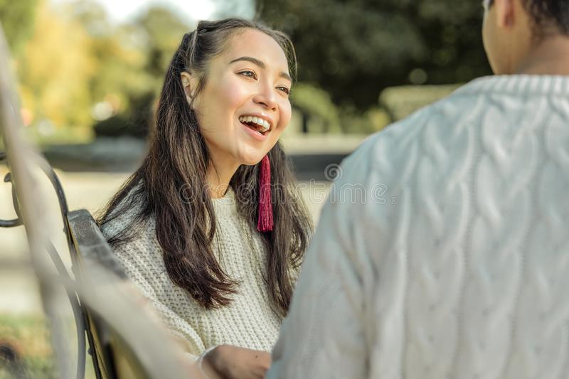 Excited dark-haired girl being entertained while having conversation. Break with girlfriend. Excited dark-haired girl being entertained while having conversation royalty free stock image