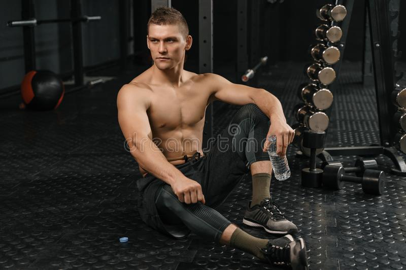 Break after hard crossfit training. Portrait of young sporty man with bottle stock image