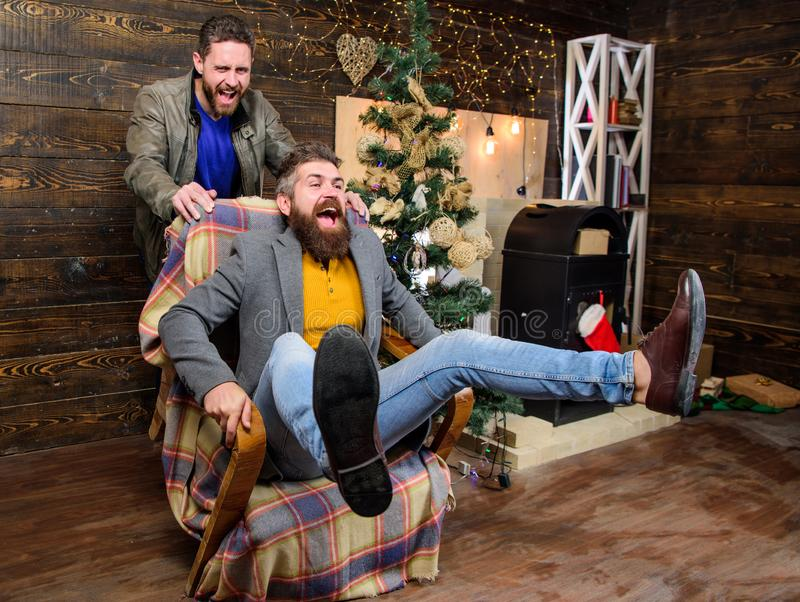 Break into new year with fun. Best friend having fun on christmas eve. Man push armchair with friend. Cheerful men stock photography