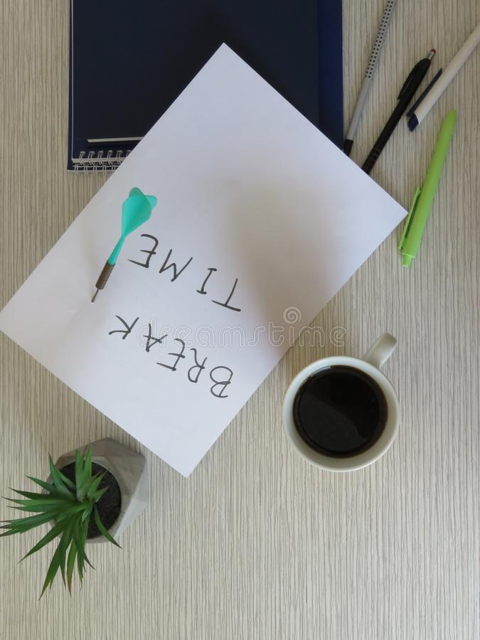 Break Time Concept. Relaxation. Office desk table with break time note, notebooks, supplies, flowers and coffee cup. Top view. royalty free stock photo