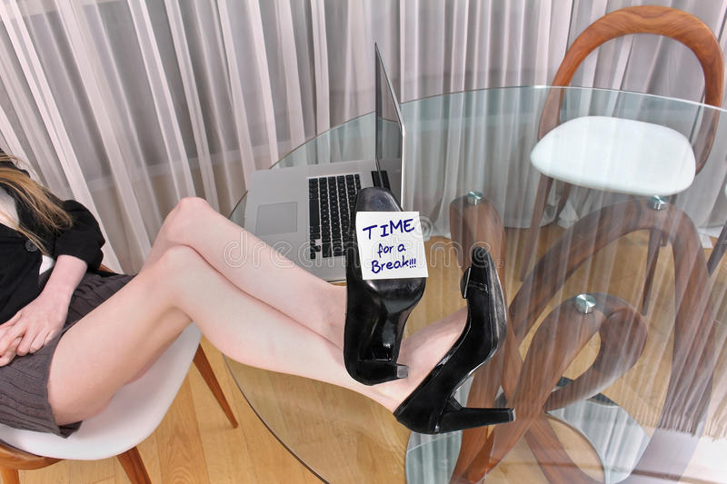 Break time. Young woman with long legs on office desk and time for break sign stock image