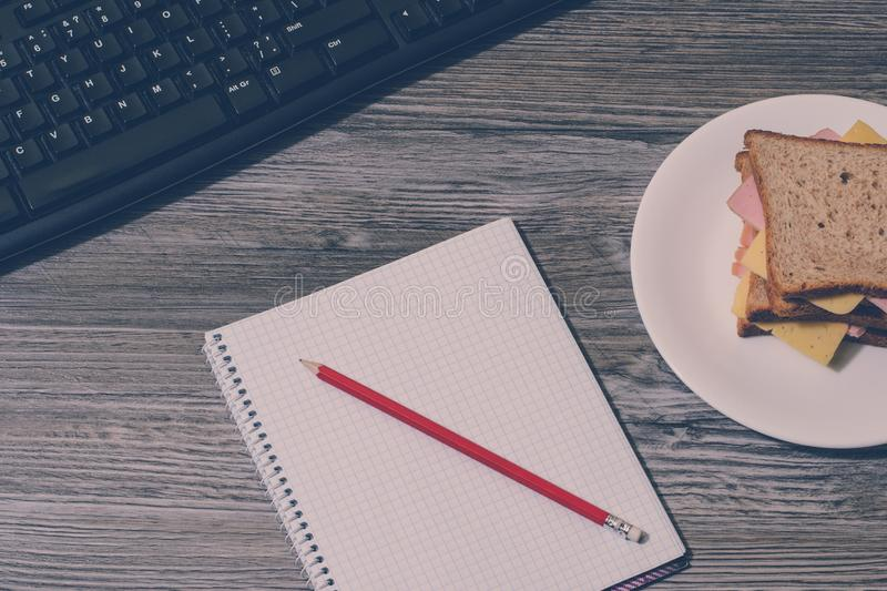 Break at work. Tasty cheese sandwich, notebook and pencil with keyboard on gray wooden background. Accent on a notebook. Vertical. View, vintage effect stock images