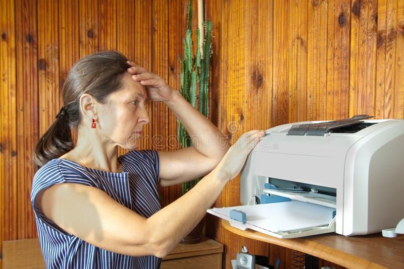 Breakage of printer. Woman printing on the printer at home.breakage royalty free stock photos