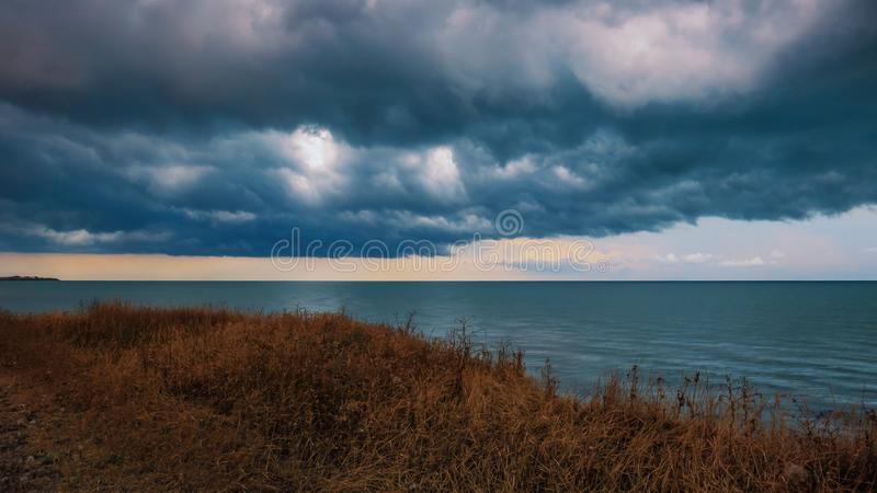 Breakage of the shore by the sea before the storm. Dramatic clouds royalty free stock photo