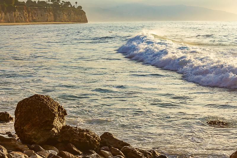 Breakaing wave with patel sunlit foam and backwash, crawling toward rocky shore. At sunrise with reflected light royalty free stock photography