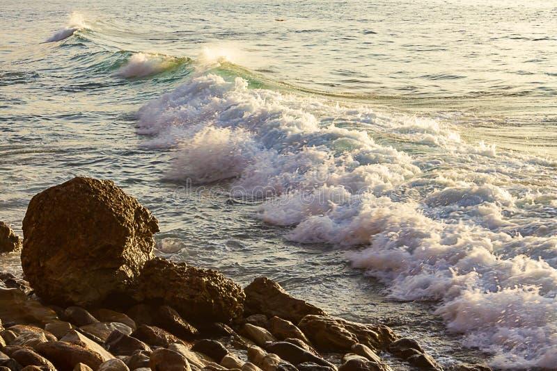 Breakaing wave with patel sunlit foam and backwash, crawling toward rocky shore. At sunrise with reflected light royalty free stock image