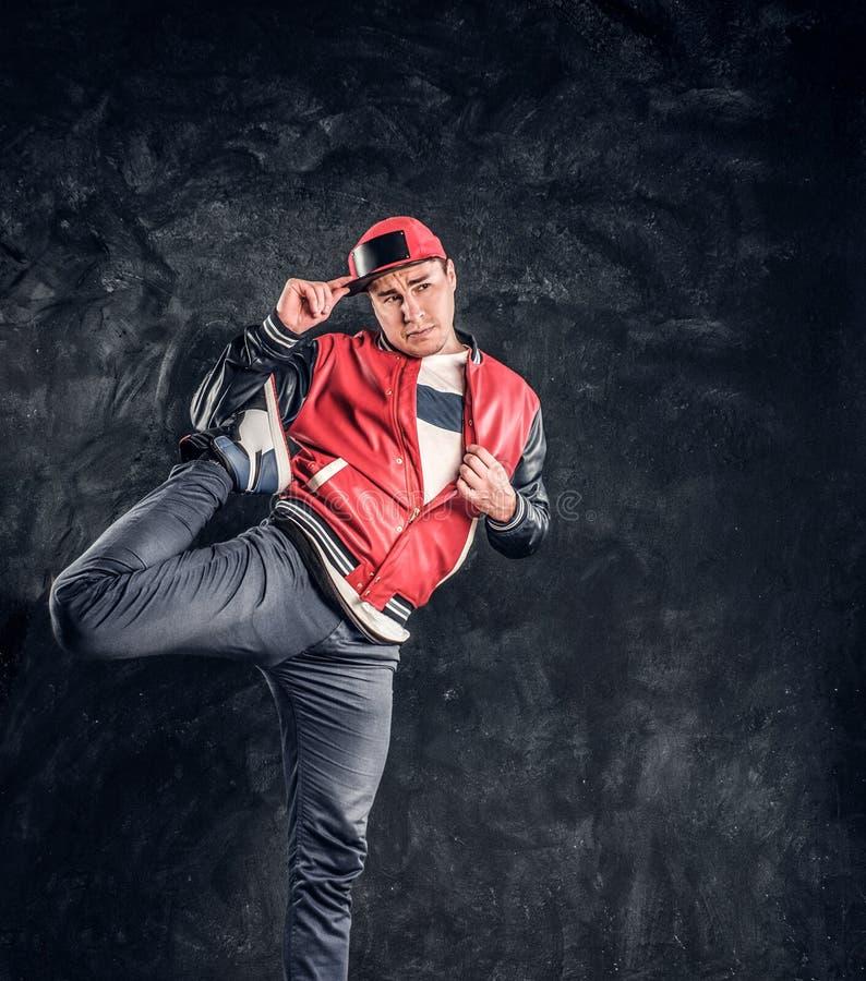Breakdancer professionale che indossa i vestiti alla moda, scaldantesi ed allungante le sue gambe per la prestazione immagine stock