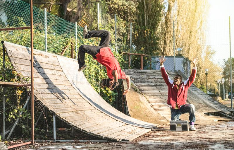 Breakdancer urbain d'athlète exécutant la secousse de saut de saut périlleux au parc de patin photo stock