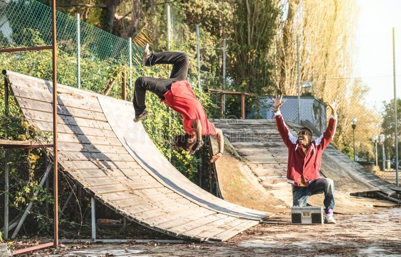 Breakdancer urbano do atleta que executa a aleta do salto do salto mortal no parque do patim foto de stock