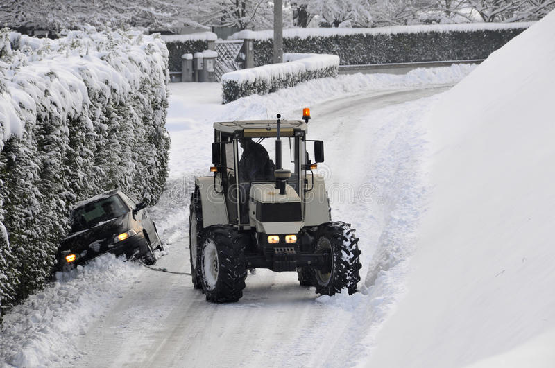 Breakdown service. A tractor is helping a car blocked in the ice royalty free stock image