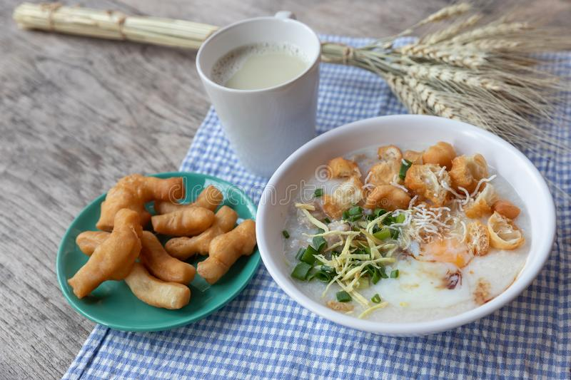 Breakfase meal. Congee or Rice porridge minced pork, boiled egg with soy milk and Chinese deep fried double dough stick.  royalty free stock photo