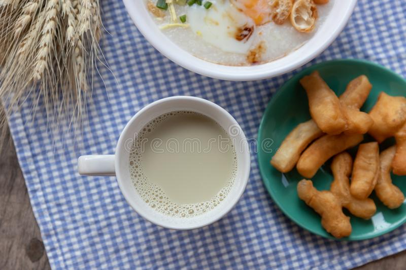 Breakfase meal. Congee or Rice porridge minced pork, boiled egg with soy milk and Chinese deep fried double dough stick.  royalty free stock photography