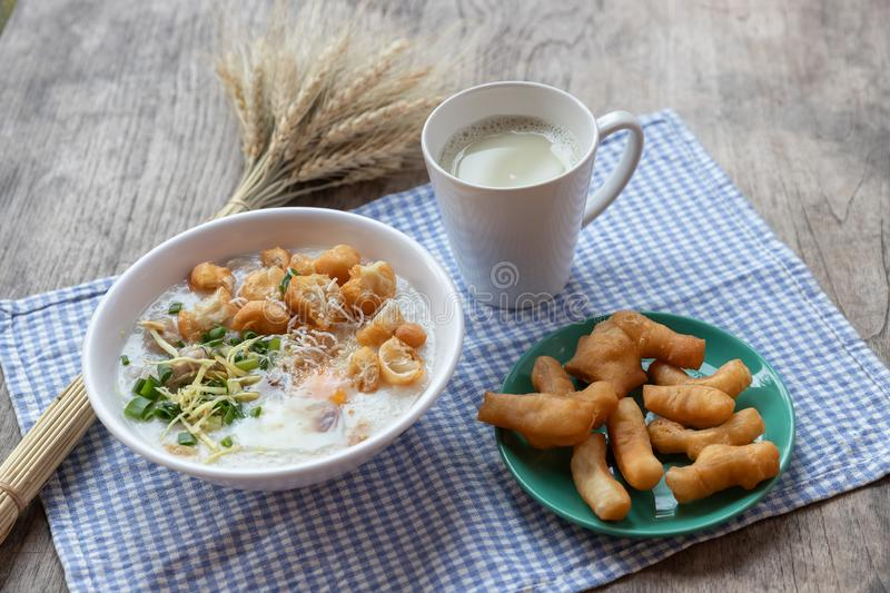 Breakfase meal. Congee or Rice porridge minced pork, boiled egg with soy milk and Chinese deep fried double dough stick.  royalty free stock photos