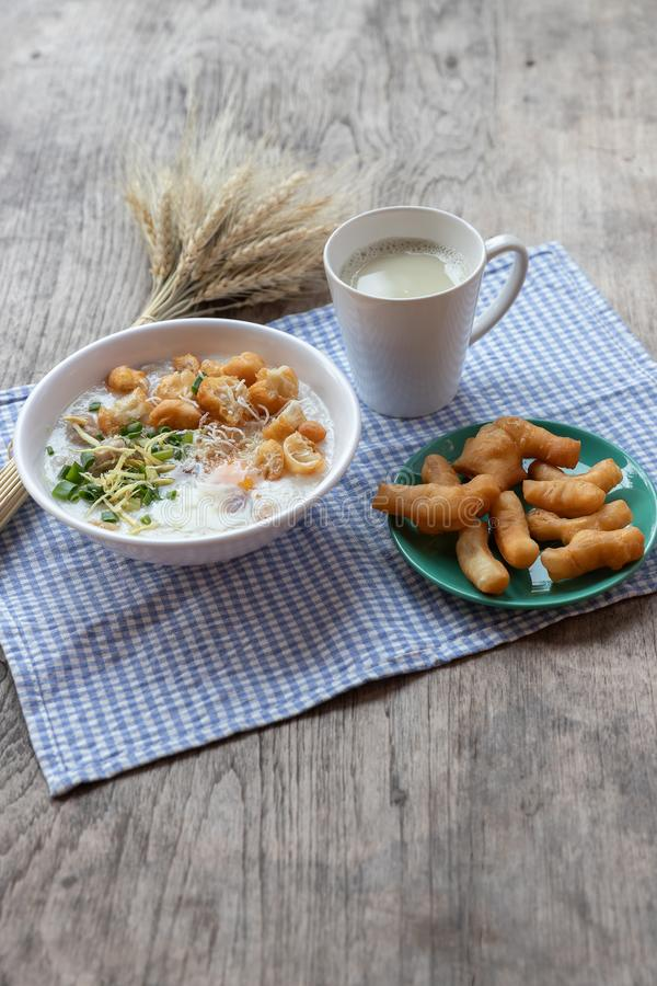 Breakfase meal. Congee or Rice porridge minced pork, boiled egg with soy milk and Chinese deep fried double dough stick.  stock image